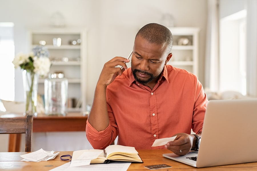 Man sitting at a desk on the phone, paying bills.