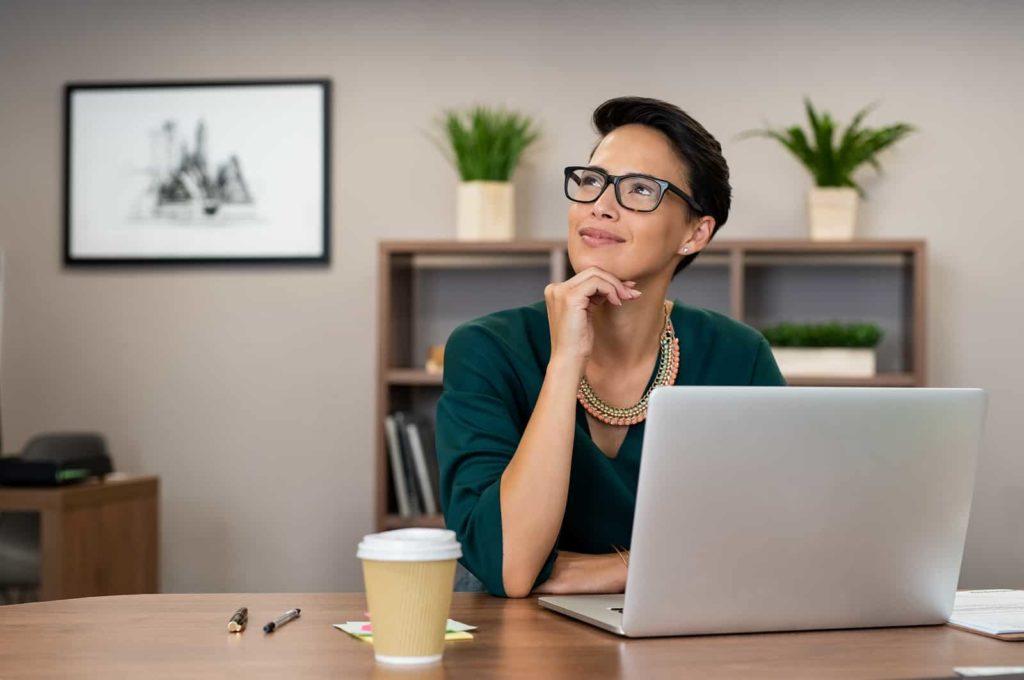 Woman sitting at laptop thinking.