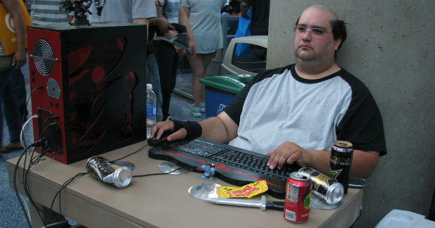 bald man sitting at desk of empty cans while playing video games