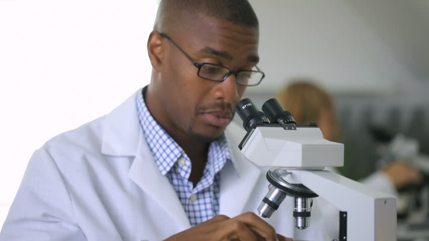 black scientist wearing glasses and a lab coat looking into a microscope