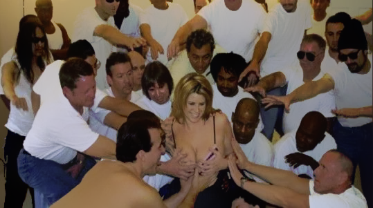 Pornstar Lisa Sparxxx surrounded by men in white shirts all reaching to touch her