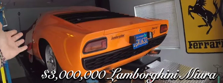 an orange lamborghini miura in a garage on a lift with a yellow ferrari sign in the background