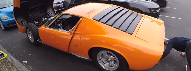 an orange lamborghini muira with the hood open and a man looking underneath