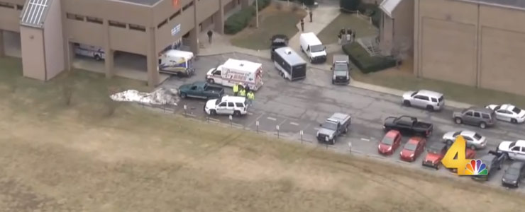 an aerial view of the aftermath of the kentucky high school shooting with multiple cars and police and emergency vehicles