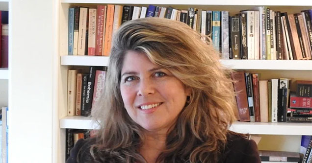 Naomi Wolf, author of the book, 'Outrages,' sits in front of a bookshelf.
