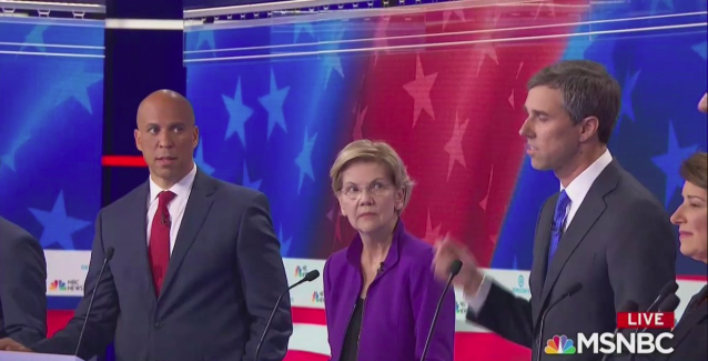 Cory Booker Elizabeth Warren and Beto O'Rouke standing together on the Democratic Debate stage