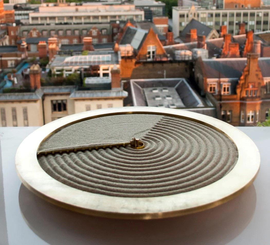 view of a city from above, round sand clock that draws circles during the am hours then erases them during the pm hours