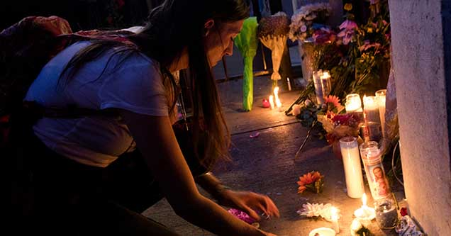 Woman lights a candle for victims of a mass shooting