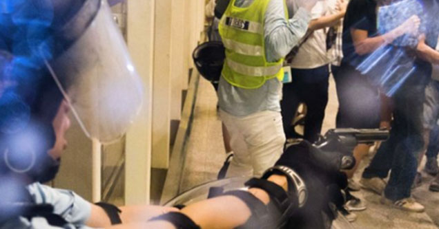 A police officer at the Hong Kong International Airport pulls a gun on protestors occupying the airport after getting attacked.