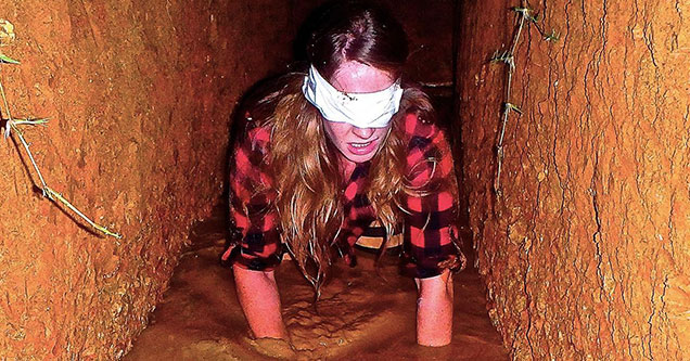 Blindfolded woman crawling through mud at the McKamey Manor