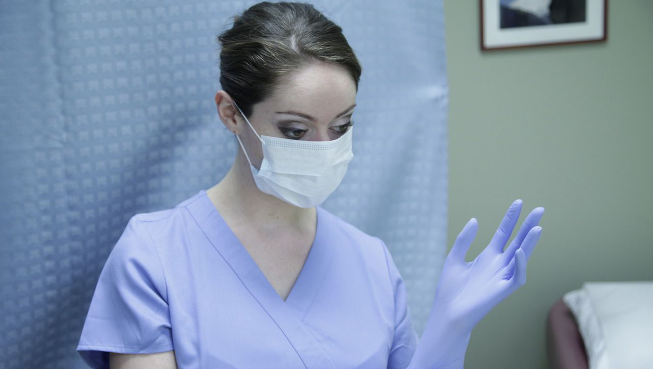 woman medical professional putting on rubber gloves