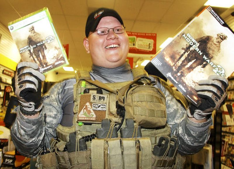 guy holding two copies of video game