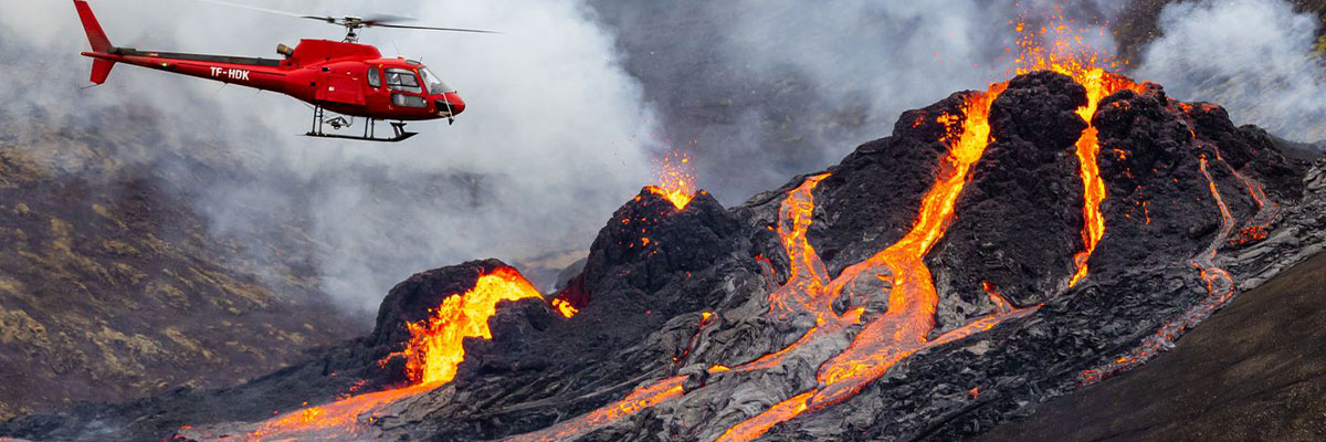 Helicopter flying over lava flow from a volcano