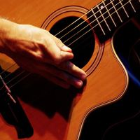 Acoustic guitar with hand of player