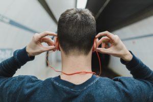 man-listening-to-earphones-in-subway