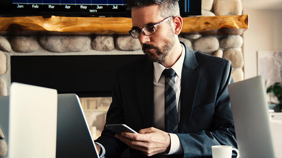 man at computer on phone