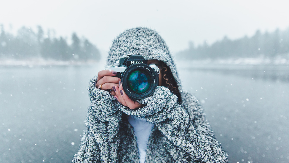 woman taking a picture outside in the winter
