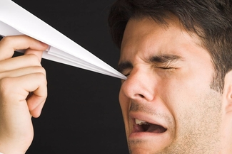 man poking eye with paper airp 325x217