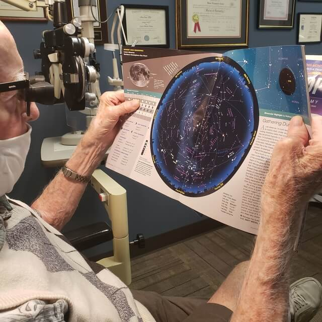 senior man reading using low vision glasses