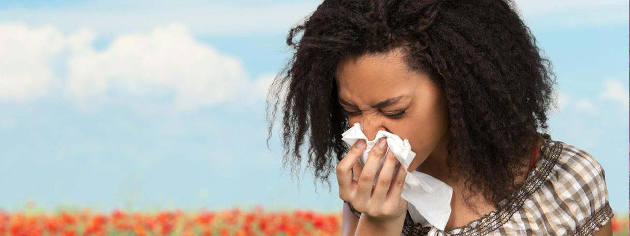 Woman with eye allergies, blowing her nose