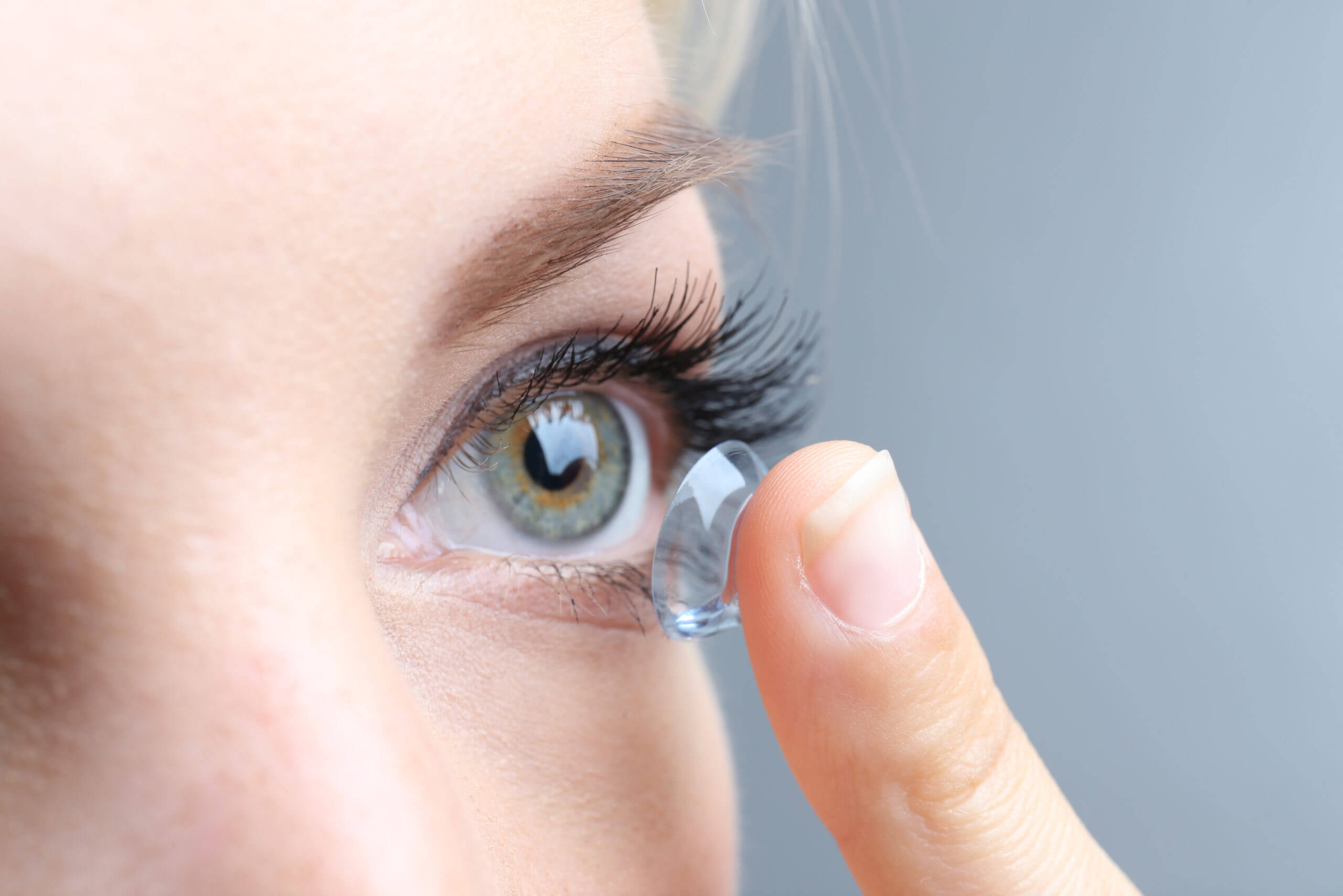 brunette woman putting in contact lenses