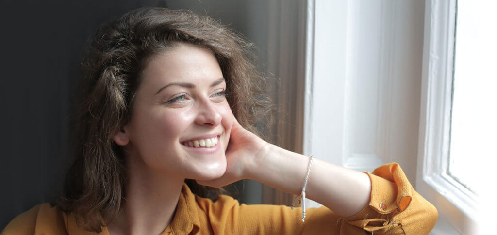 woman smiling looking into distance 1024x485