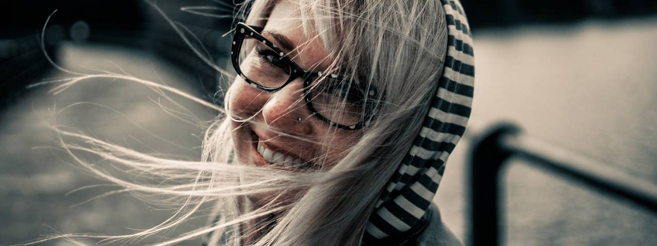 Girl wearing glasses on a windy day