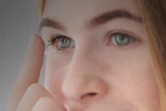 Woman inserting contact lens in her eye in Columbus, Ohio