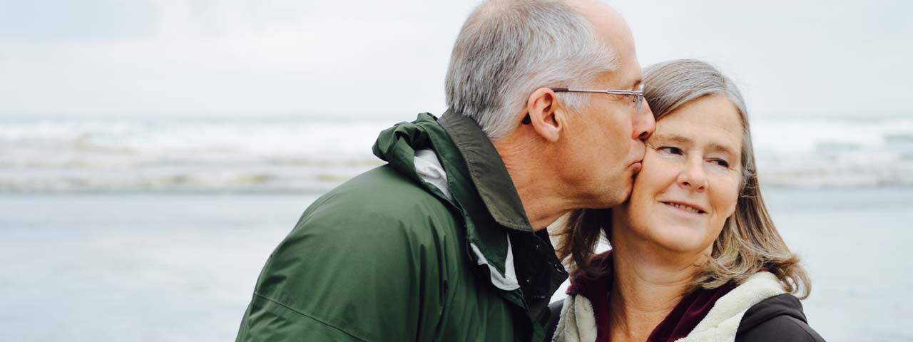 Older man with presbyopia kissing his wife near the beach