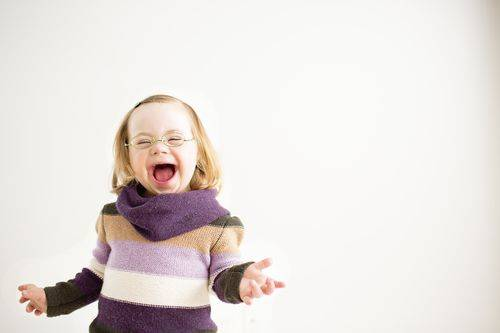 Smiling girl with Down Syndrome wearing glasses