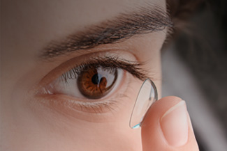 Girl With Brown Eyes Inserting a Contact Lens
