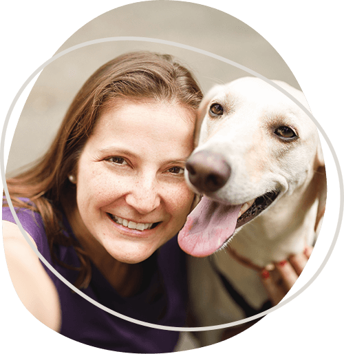 woman-smiling-while-holding-a-golden-retriever.png