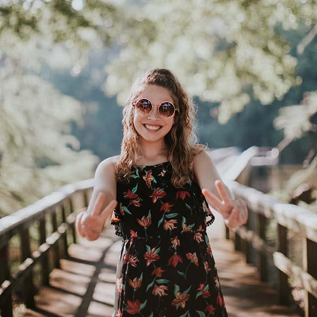 Woman wearing suglasses, peace signs on bridge