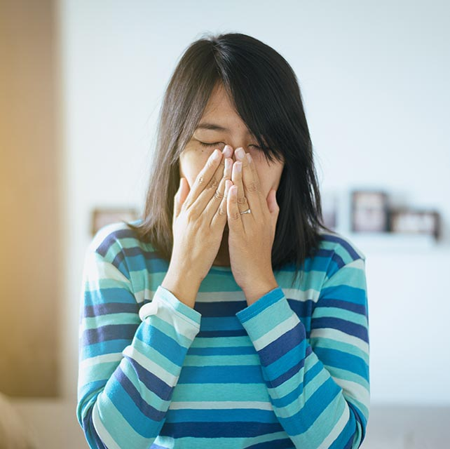 Asian woman covering her mouth as she sneezes in Glassboro, NJ