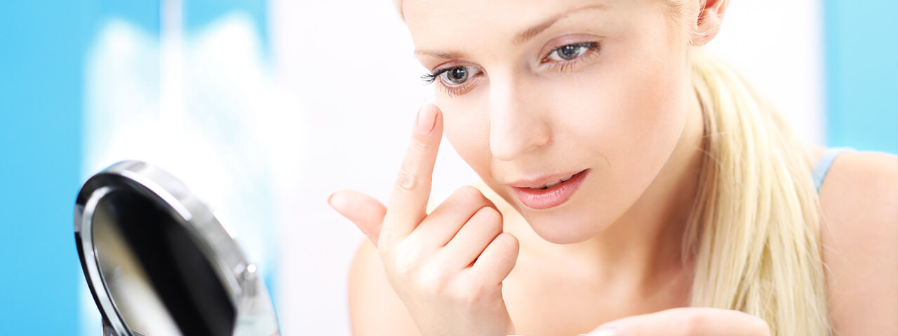 Woman using mirror to insert contact lens