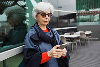 Serious Focused Lady In Sunglasses Using Mobile Phone. Grey Hair