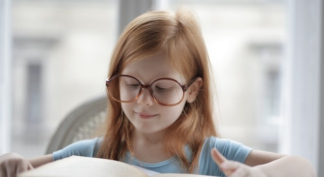 little-girl-wearing-glasses-reading-a-book