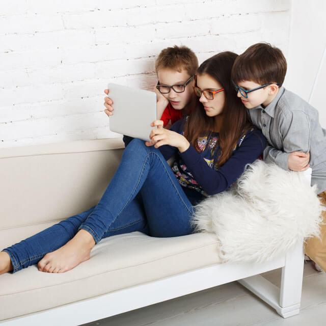 children with glasses looking at ipad for reviews