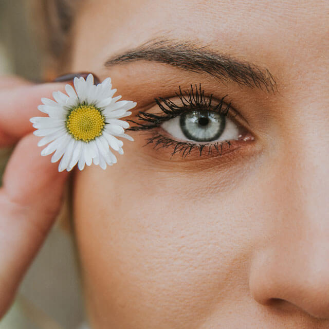Woman with hand over eye, enjoying eyesight after lasik