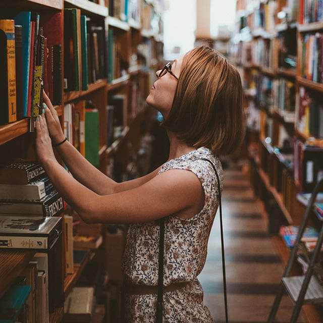 College student wearing eyeglasses, in library