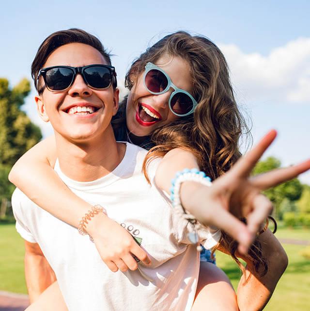 Man and woman wearing sunglasses, having fun