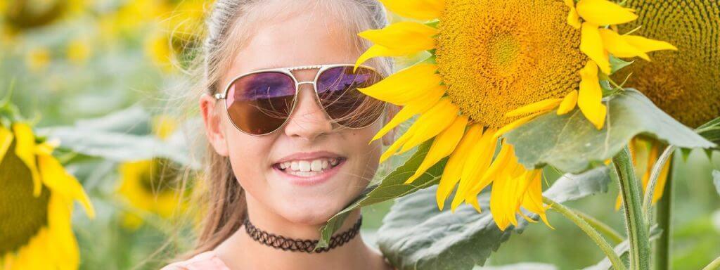 Girl wearing sunglasses in a field of sunflowers