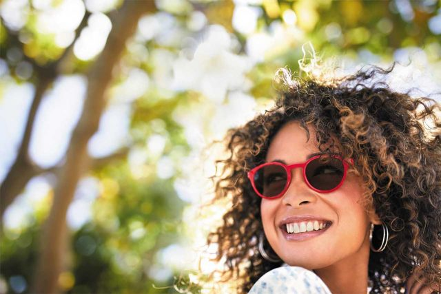 Woman smiling wearing Transitions Lenses outdoors in Copperas Cove, TX