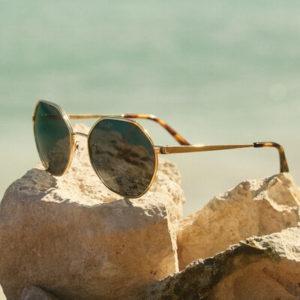 pair of michael kors sunglasses on a rock