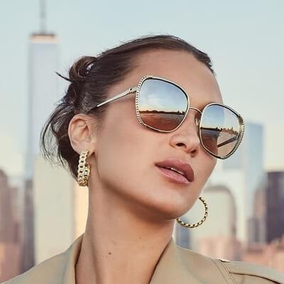 woman wearing gold tinted michael kors sunglasses
