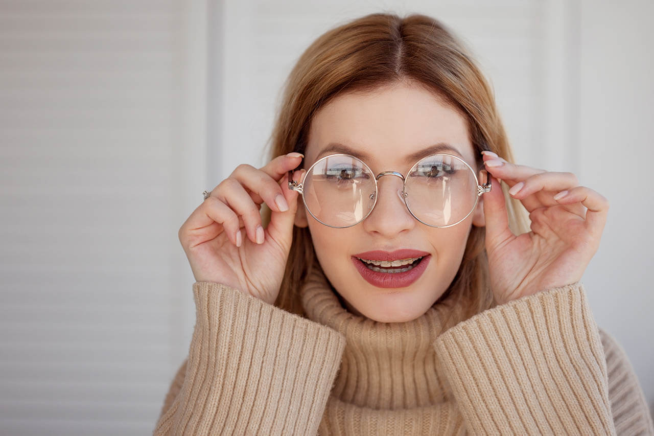 Charming Young Woman In Large Round Glasses Peering Into Somethi