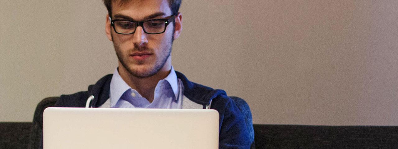 Young Man Using Laptop 1280x480