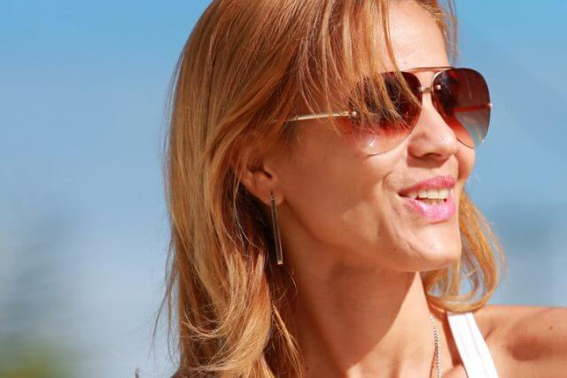 Woman wearing sunglasses, smiling