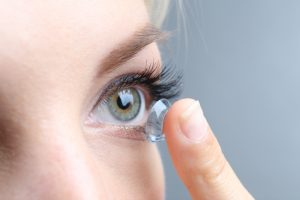 Medicine and vision concept young woman with contact lens,