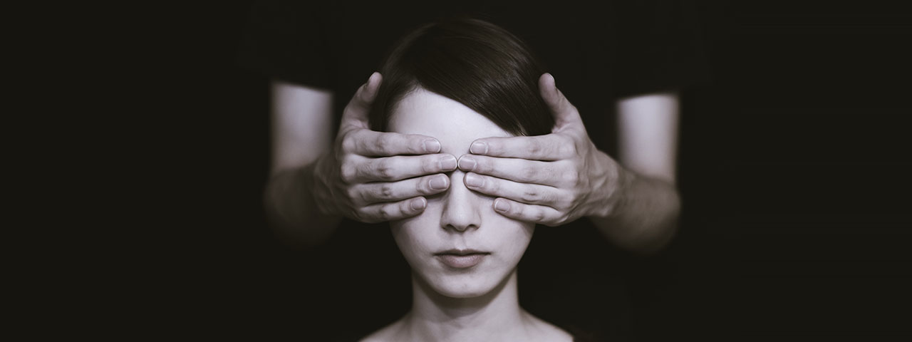 Woman with eyes covered to illustrate Severe Vision Loss or Legal Blindness